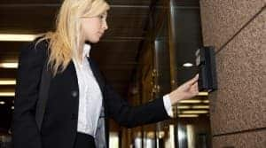 An image of a women pressing an Access Control System to open a door