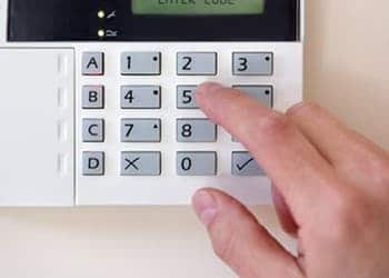 An image of someone setting an alarm system for security.