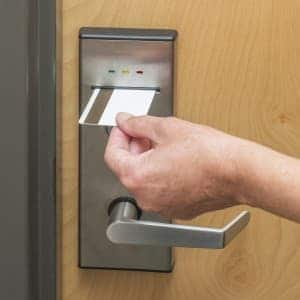 An image of a key card being used to open a door that uses access control systems