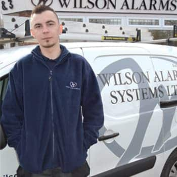 An image of a Wilson Alarm Systems employee named Gracjan Nogaj
