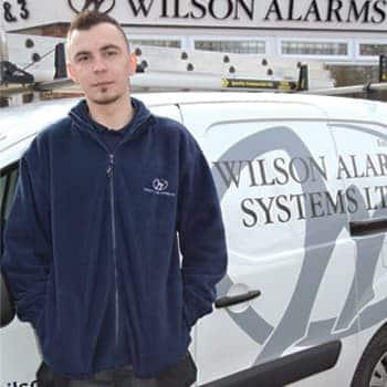 An image of a Wilson Alarm Systems employee named Gracjan Nogaj