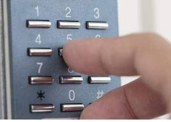A close up image of someone pressing an access control keypad