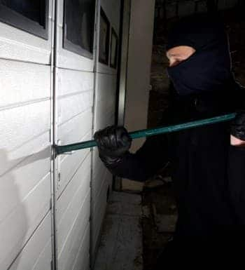 An image of a burglar trying to break entry into a locked building