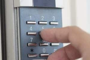 A close up image of a hand tapping numbers of a pin entry system.