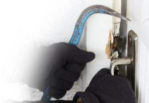 An image of black gloved hands, trying to break into a property using a crow bar.