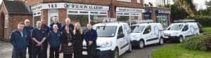 An image of the Wilson Alarm Systems Ltd team standing outside of their office, next to the company vans