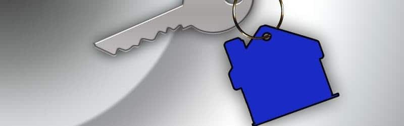 An image showing a silver key with a blue keyring the shape of a house attached.