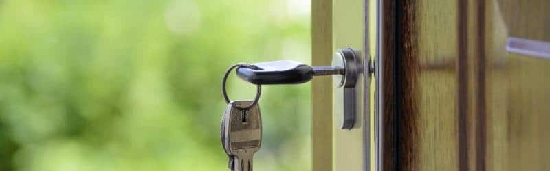 An image of keys in a lock on an open front door to a home, with a soft focus garden in the background