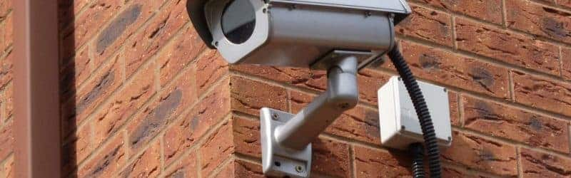 An image of a CCTV camera installed onto the side of a building