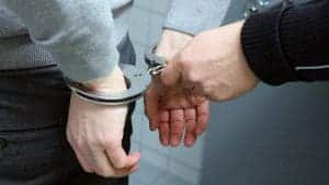 An image of a criminal being handcuffed by police.